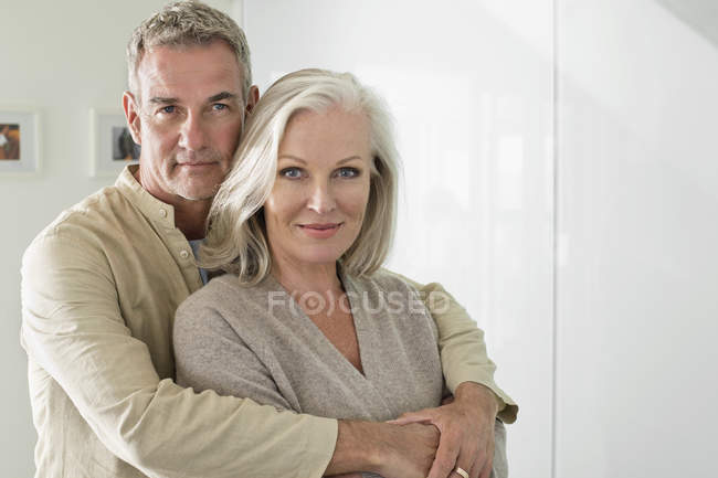 Retrato de hombre feliz abrazando esposa en casa - foto de stock
