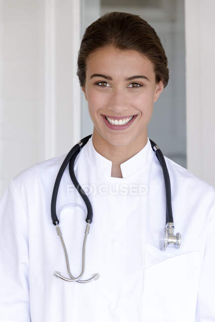 Portrait of happy female doctor standing and looking at camera — Stock Photo