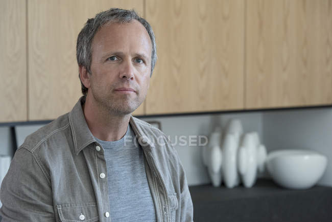 Portrait of mature man standing in kitchen — Stock Photo