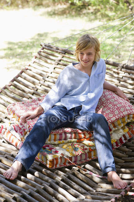 Smiling teenage boy looking away while sitting in hammock outdoors — Stock Photo