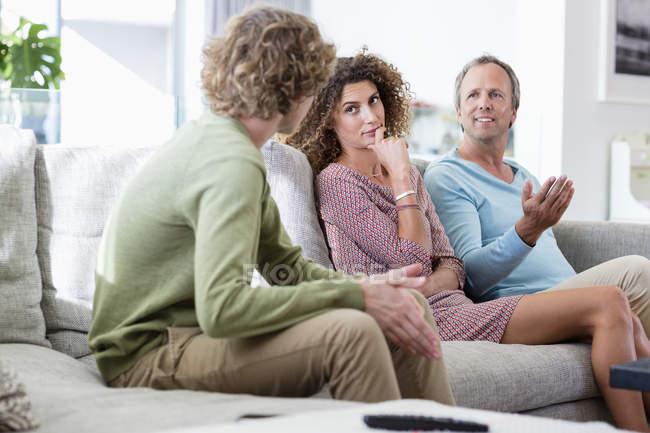 Familia feliz hablando en el sofá en la sala de estar en casa - foto de stock