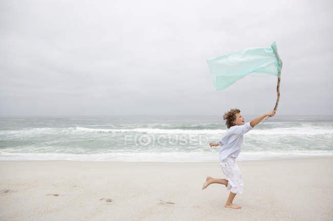 Boy running while holding flag on sandy beach — Stock Photo
