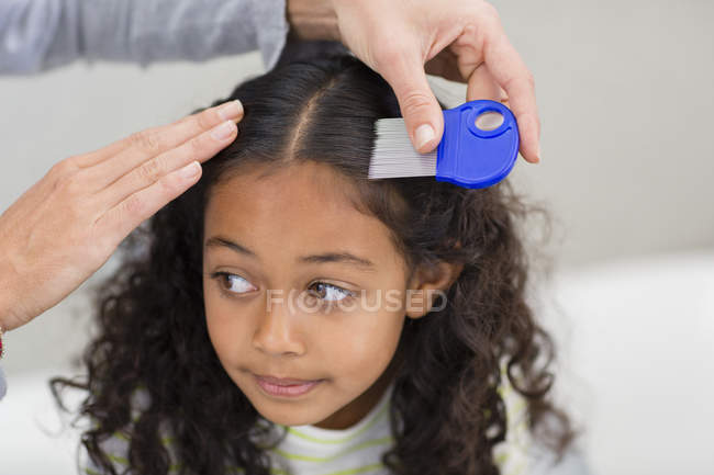Mother using lice comb on daughter hair — Stock Photo
