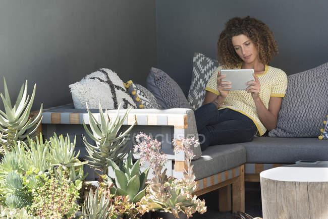 Жінка, сидячи на канапі в домашніх умовах і за допомогою цифровий планшетний — стокове фото