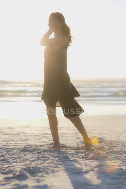 Sensual young woman standing on beach in sunlight — Stock Photo