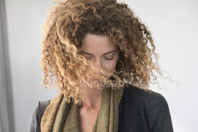Gros plan de femme avec des cheveux bouclés, regardant vers le bas — Photo de stock