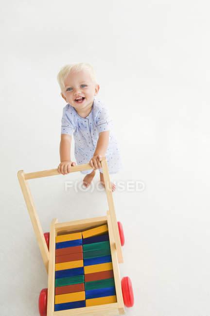 Loira menino empurrando carrinho no fundo branco — Fotografia de Stock