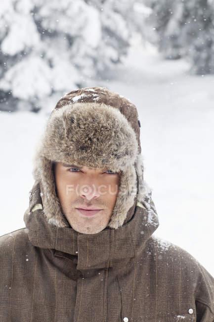 Giovane uomo in abiti invernali guardando macchina fotografica in natura — Foto stock