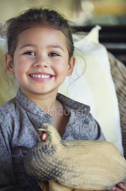 Ritratto di bambina sorridente con in braccio un modello di tacchino — Foto stock