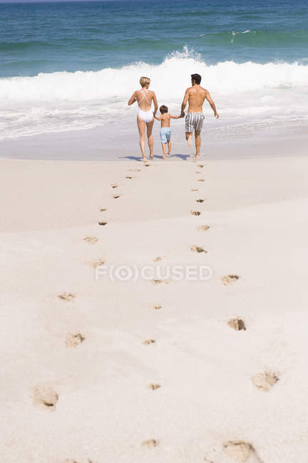 Footsteps on sandy beach with family on background — Stock Photo