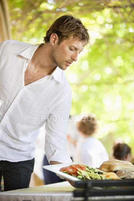 Young man serving salad on wooden table outdoors — Stockfoto