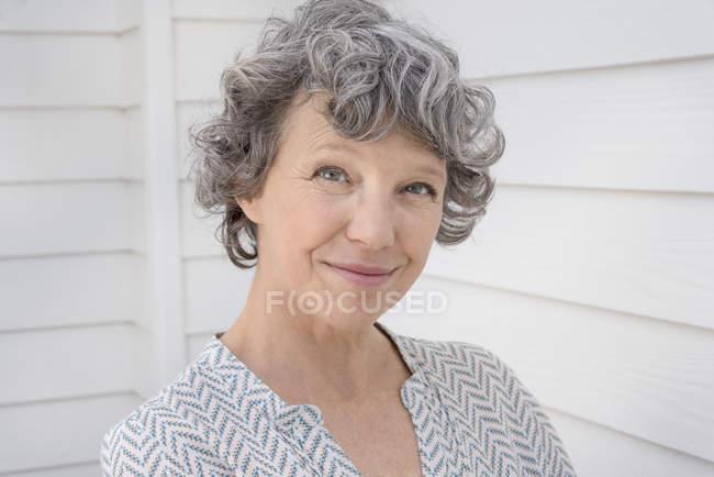 Retrato de feliz mujer madura delante de pared blanco - foto de stock