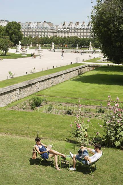 Uomo che utilizza laptop e donna che legge una rivista in giardino, Jardin des Tuileries, Parigi, Ile-de-France, Francia — Foto stock