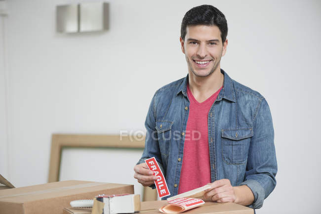 Man sticking Fragile sticker on cardboard boxes and looking at camera — Stock Photo