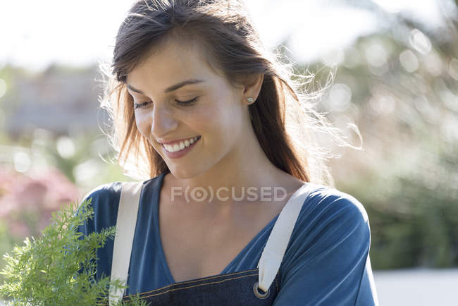Close-up of smiling young woman in apron holding plant in garden — Stockfoto
