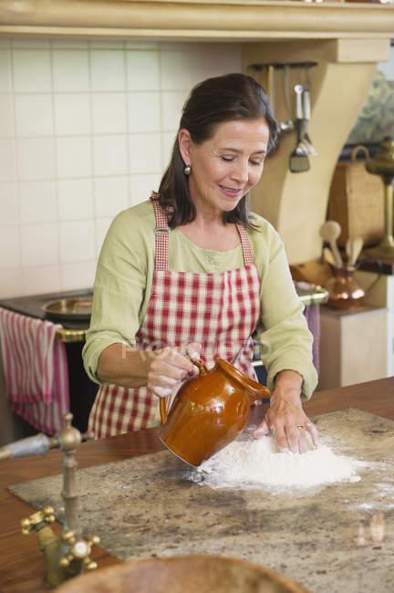 Lächelnd senior Frau gießt Wasser in Mehl auf Küche Tischplatte — Stockfoto