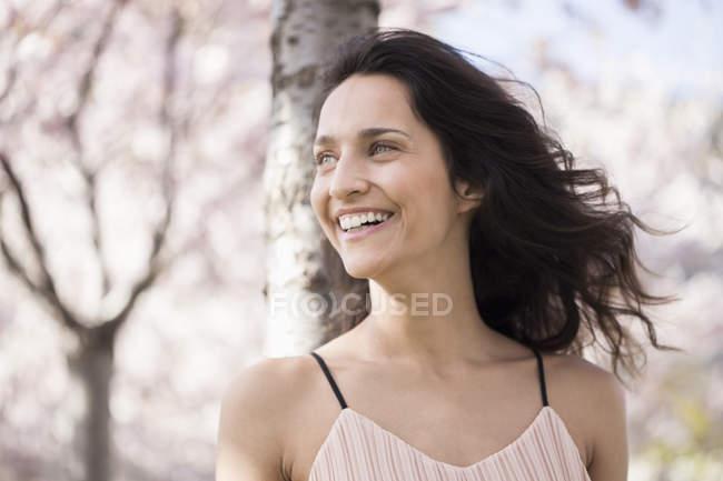 Sorrindo mulher apoiando-se no tronco da árvore e olhando para longe — Fotografia de Stock