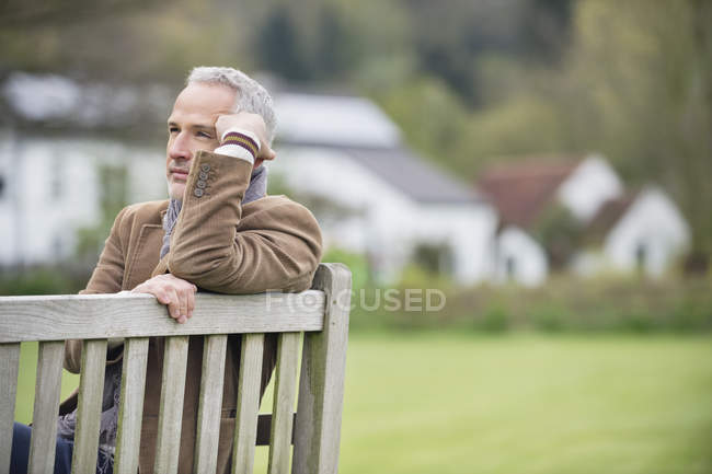 Uomo maturo premuroso seduto sulla panchina nel parco — Foto stock