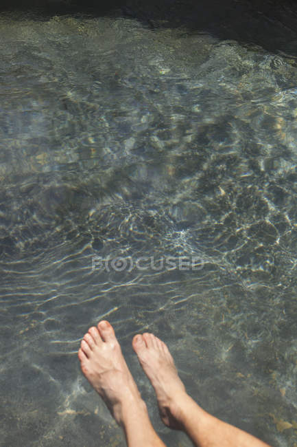 Closeup of human legs in ripple clean water — Stock Photo