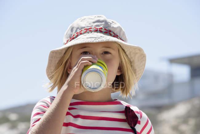 Дівчинка в капелюсі, насолоджуючись прохолодними напоями на свіжому повітрі — стокове фото