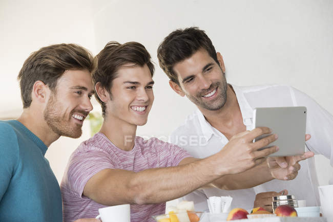Happy male friends taking selfie with tablet on breakfast table at home — Stock Photo