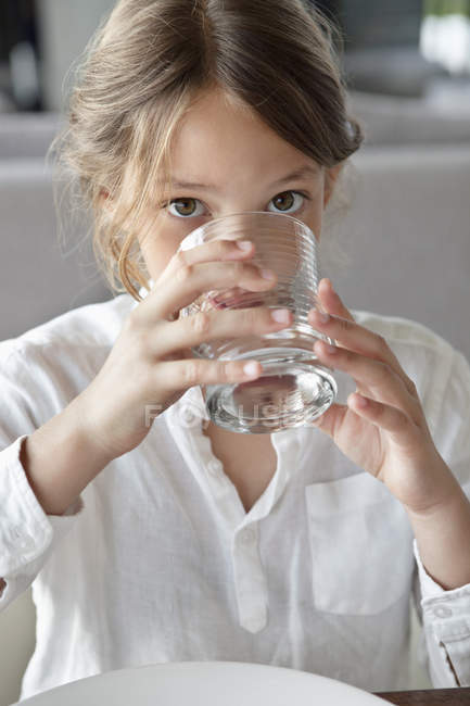 Portrait of little girl drinking water in kitchen — Stock Photo