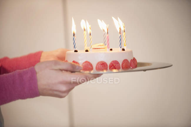 Close-up of female hands holding birthday cake — Stock Photo