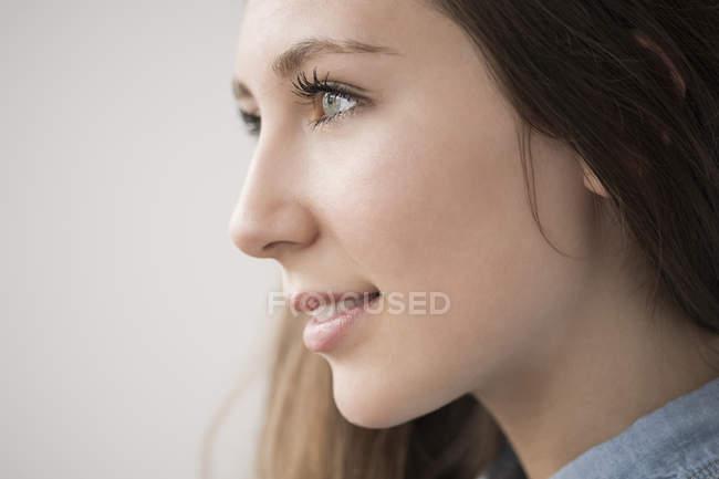 Лицо счастливой девочки-подростка с натуральным макияжем, отворачивающимся — стоковое фото