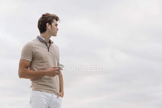 Young man holding smartphone under cloudy sky - foto de stock