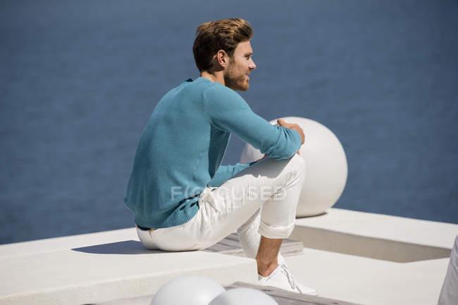 Giovane uomo rilassato seduto sulla terrazza sulla riva del lago — Foto stock
