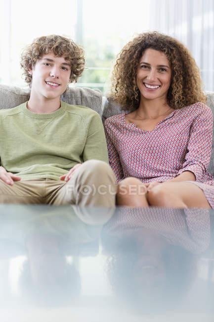 Retrato da matriz e do filho felizes que sentam-se no sofá na sala de visitas — Fotografia de Stock