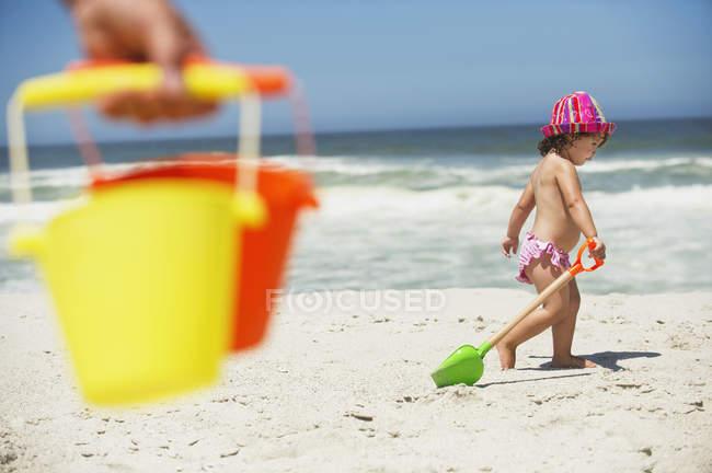 Kleines Mädchen läuft mit Sandschaufel am Sandstrand — Stockfoto