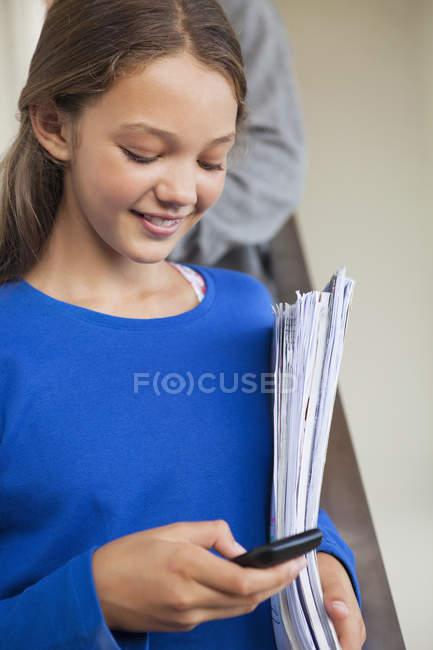 Крупным планом улыбается девушка текстовых сообщений с мобильного телефона — стоковое фото