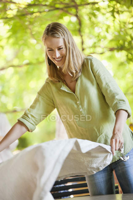 Smiling woman holding tablecloth in garden — Stock Photo
