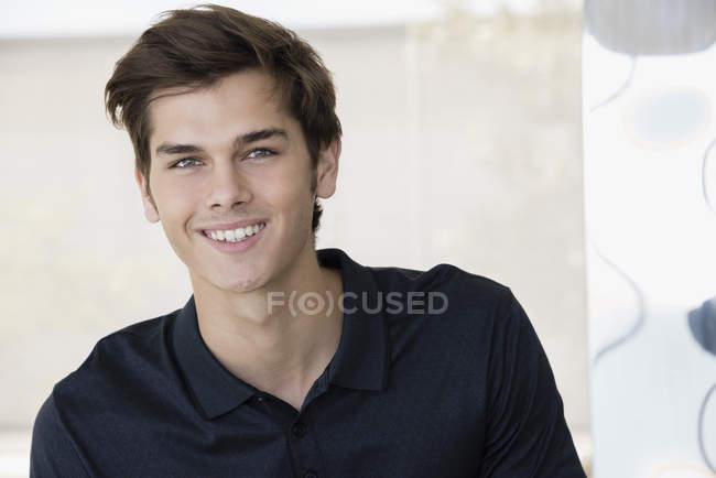 Портрет усміхнений молодих красенем в чорні сорочки поло — стокове фото