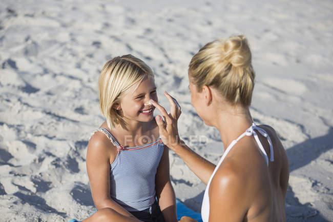 Женщина применения ВС экрана на дочь нос на песчаном пляже — стоковое фото