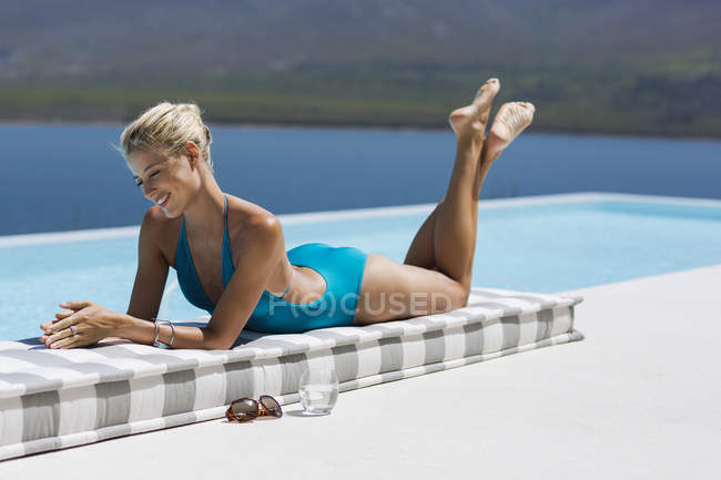 Happy blond woman relaxing at poolside — Stock Photo