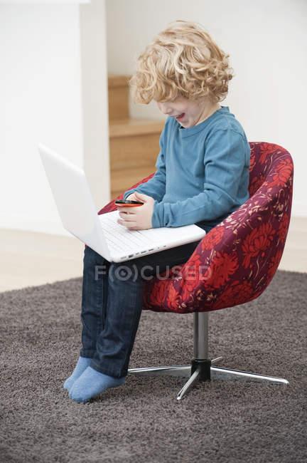 Junge spielt zu Hause im Sessel mit Handy und Laptop — Stockfoto