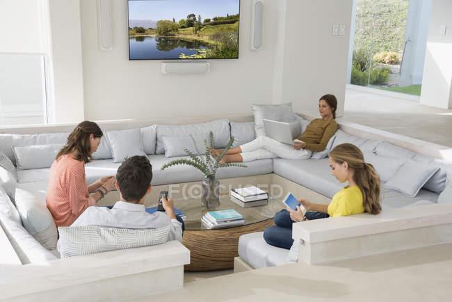 Familia de múltiples generaciones usando gadgets en la sala de estar - foto de stock