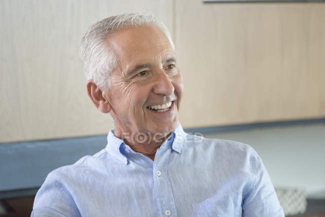Portrait of happy senior man in shirt looking away — Stock Photo