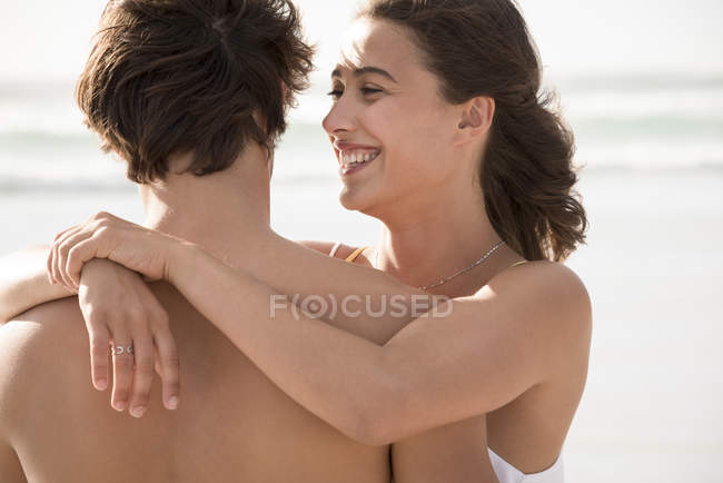 Happy young woman embracing boyfriend on beach — Stock Photo
