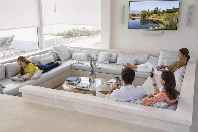 Famiglia multi-generazione utilizzando gadget in soggiorno — Foto stock