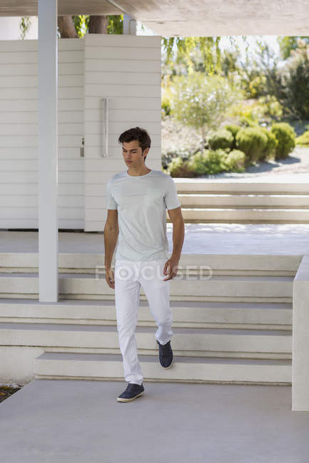 Young man walking downstairs outdoors — Stock Photo