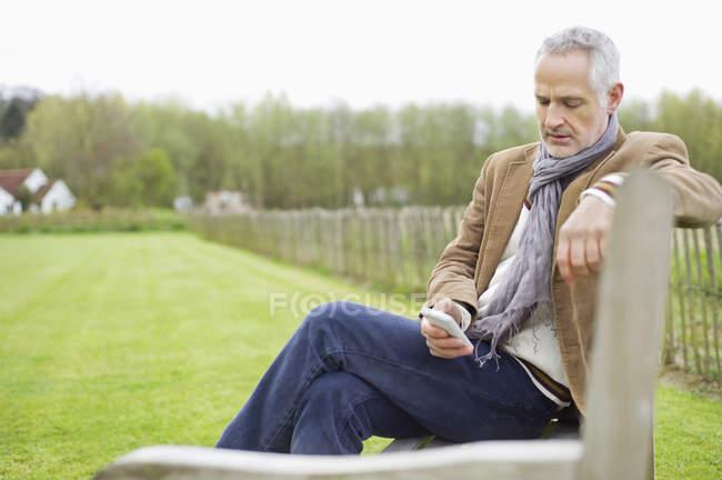 Messaggi con cellulare seduti sulla panchina in campo di testo uomo — Foto stock