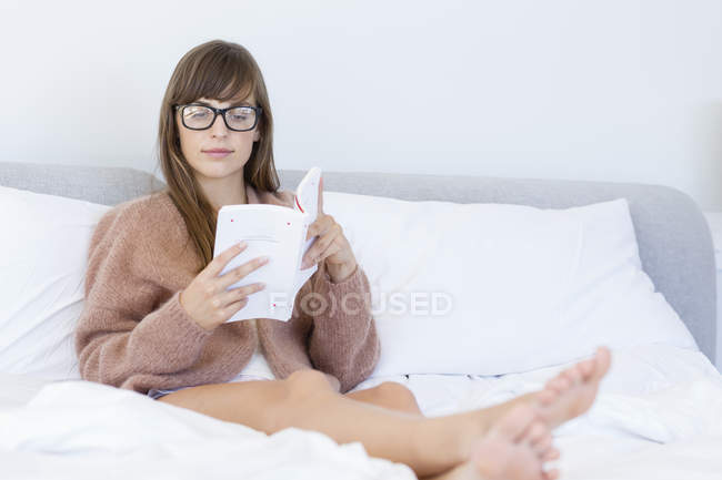 Woman sitting on comfy bed and reading book — Stock Photo
