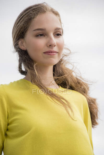 Close-up of thoughtful teenage girl in yellow sweater — Stock Photo