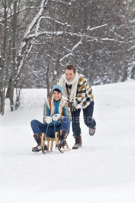 Young man pushing woman on sled in winter countryside — Stock Photo