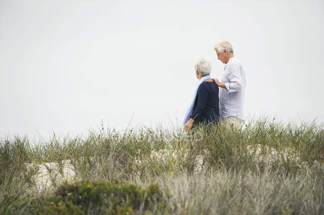 Happy senior couple walking on path on coast — Stock Photo