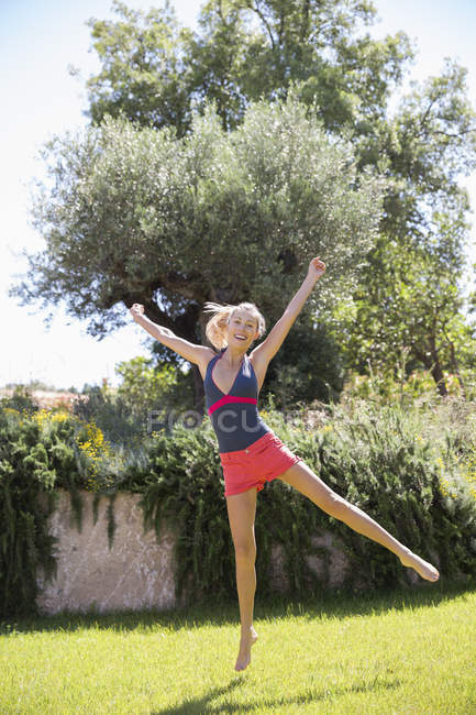Happy woman exercising in sunny garden with arms outstretched — Stock Photo