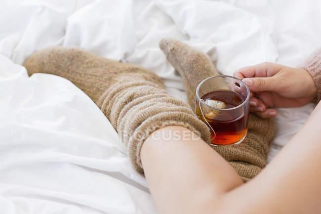 Крупный план женщины с чашкой травяного чая в постели — стоковое фото